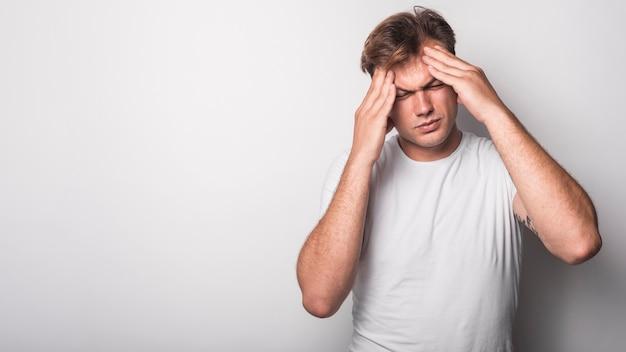 Nahaufnahme des jungen mannes leidend unter den kopfschmerzen getrennt über weißem hintergrund Kostenlose Fotos