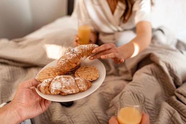Nahaufnahme des jungen paares mit köstlichem frühstück im bett. romantischer morgen mit frischen croissants, keksen und saft Premium Fotos