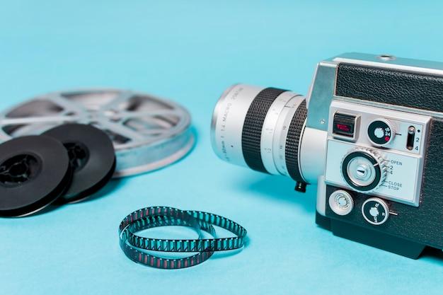 Nahaufnahme des kamerarecorders mit filmrollen und filmstreifen auf blauem hintergrund Kostenlose Fotos