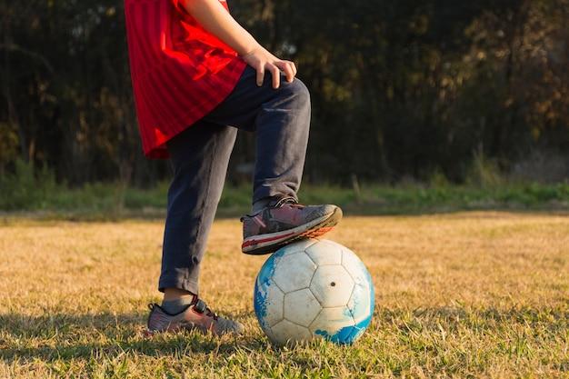 Nahaufnahme des kindes spielend mit fußball im park Kostenlose Fotos