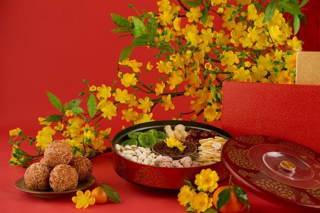 Nahaufnahme des köstlichen lebensmittels des neuen jahres auf einer gedienten tabelle, roter hintergrund Kostenlose Fotos