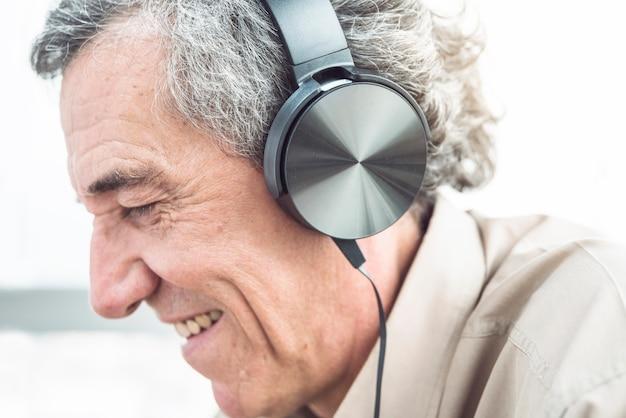 Nahaufnahme des lächelnden älteren mannes, der musik auf kopfhörer genießt Kostenlose Fotos