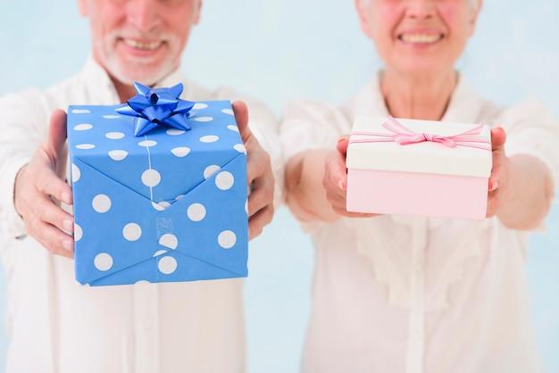 Nahaufnahme des lächelnden ehemanns und der frau, die geburtstagsgeschenkbox geben Kostenlose Fotos