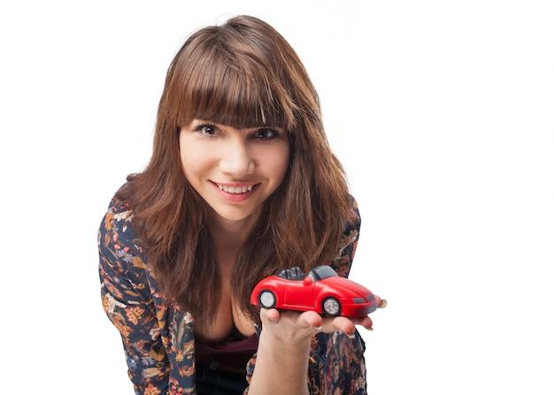 Nahaufnahme des lächelnden mädchen mit einem spielzeugauto zeigt Kostenlose Fotos