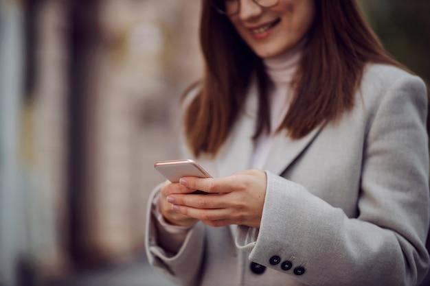 Nahaufnahme des lächelnden mädchens in einem mantel, der auf der straße steht und smartphone für sms verwendet. Premium Fotos