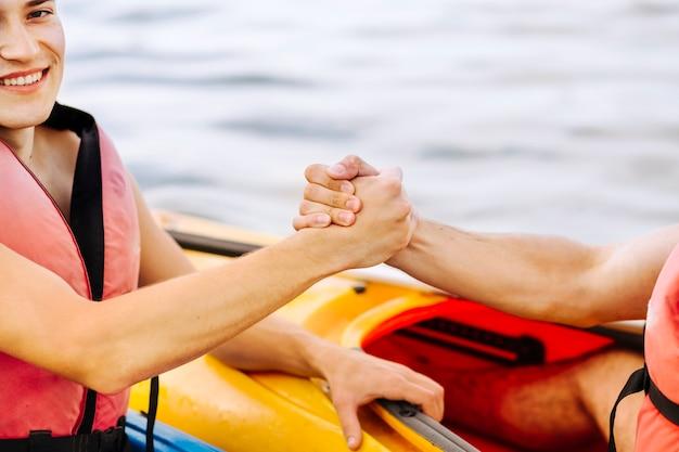 Nahaufnahme des lächelnden männlichen kayaker, der freundhand hält Kostenlose Fotos