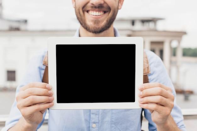 Nahaufnahme des lächelnden mannes digitale tablette zeigend Kostenlose Fotos