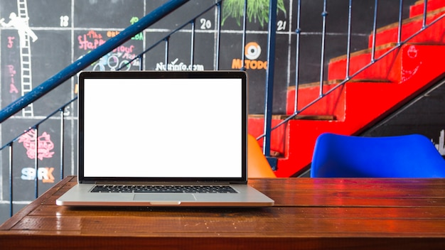 Nahaufnahme des laptops auf hölzernem schreibtisch vor treppenhaus Kostenlose Fotos