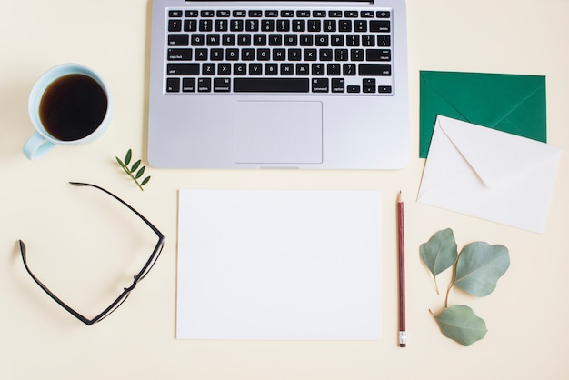 Nahaufnahme des laptops mit umschlag; papier; bleistift; brille; teetasse und brille auf farbigem hintergrund Kostenlose Fotos