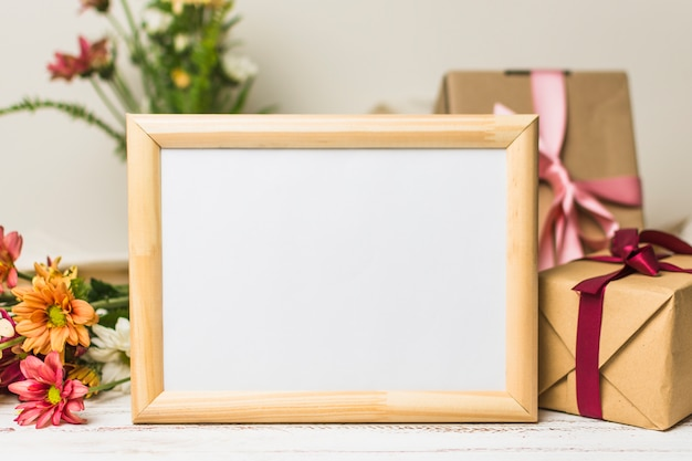 Nahaufnahme des leeren holzrahmens mit geschenk und blumen Kostenlose Fotos