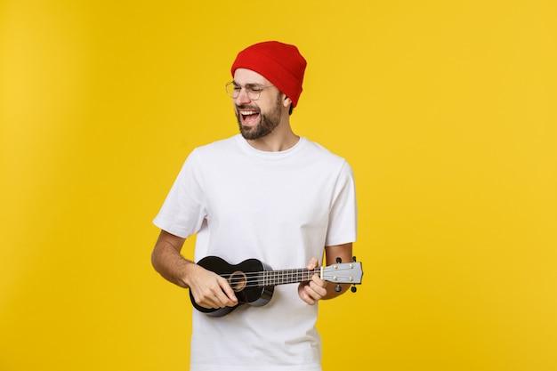 Nahaufnahme des lustigen jungen mannes, der eine gitarre spielt. isoliert auf gelbgold Premium Fotos