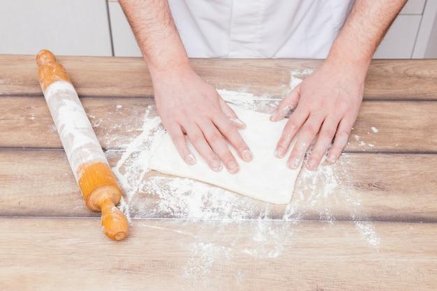 Nahaufnahme des männlichen bäckers den teig auf holztisch vorbereitend Kostenlose Fotos