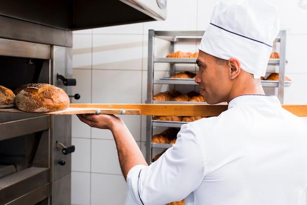Nahaufnahme des männlichen bäckers in der uniform, die mit schaufel frisch gebackenes brot vom ofen herausnimmt Kostenlose Fotos