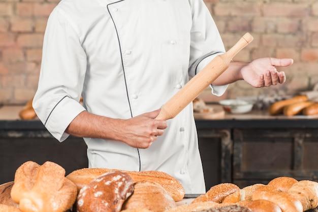 Nahaufnahme des männlichen bäckers stehend hinter der tabelle, die nudelholz hält Kostenlose Fotos