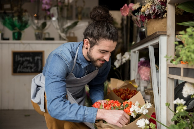 Nahaufnahme des männlichen floristen blumenblumenstrauß im blumenladen schaffend Kostenlose Fotos