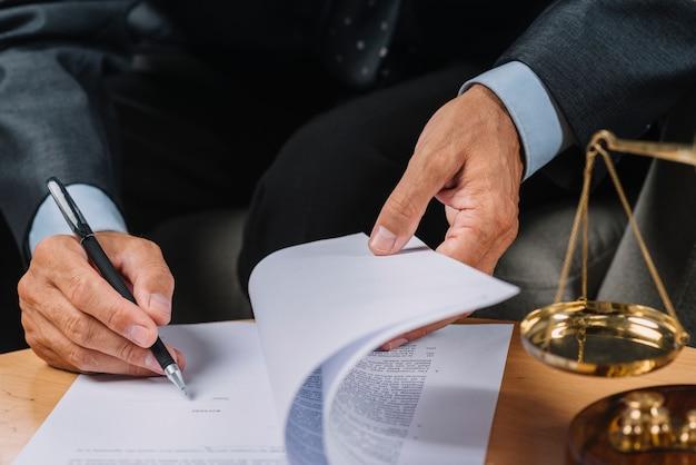 Nahaufnahme des männlichen rechtsanwalts das vertragsdokument auf dem schreibtisch unterzeichnend Kostenlose Fotos