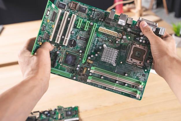 Nahaufnahme des männlichen technikers it, der computer mainboard hält Kostenlose Fotos