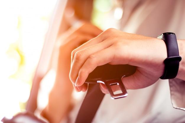 Nahaufnahme des mannbefestigungs-sicherheitsgurtes im auto, sicherheitsgurtsicherheit zuerst Premium Fotos