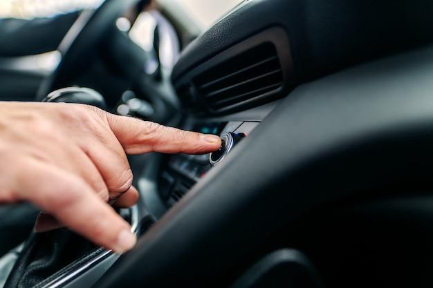 Nahaufnahme des mannes, der guten radiosender sucht, während er im auto sitzt. Premium Fotos