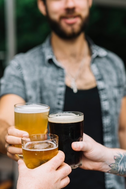 Nahaufnahme des mannes die gläser bier mit seinen freunden zujubelnd Kostenlose Fotos