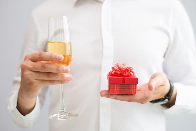 Nahaufnahme des mannes glas mit champagner und kleiner geschenkbox halten Kostenlose Fotos