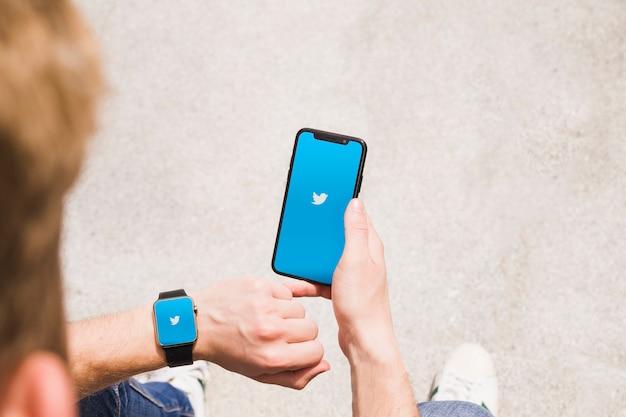 Nahaufnahme des mannes mit smartwatch und mobiltelefon, die twitter-app zeigen Kostenlose Fotos
