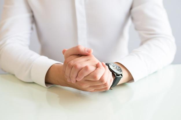 Nahaufnahme des mannes sitzend am schreibtisch mit seinen händen umklammert Kostenlose Fotos