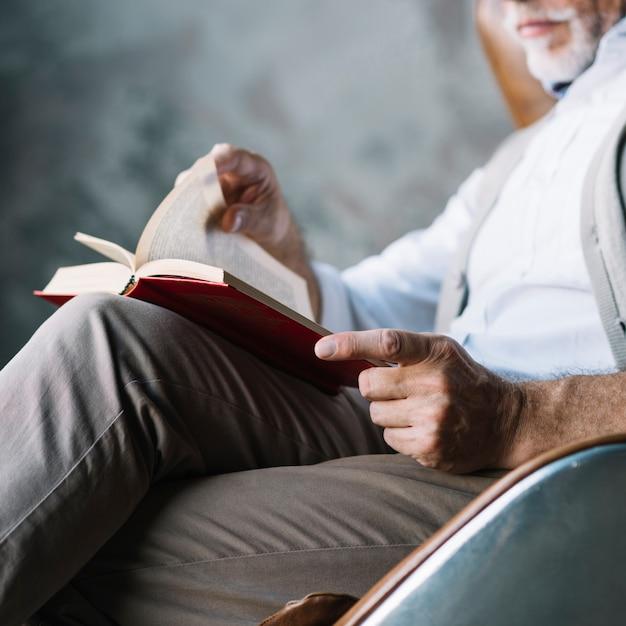 Nahaufnahme des mannes sitzend auf stuhllesebuch Kostenlose Fotos