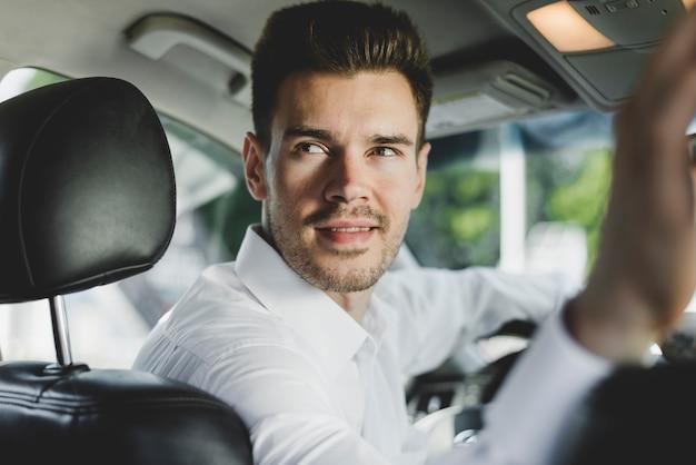 Nahaufnahme des mannes sitzend im auto, das zurück schaut Kostenlose Fotos