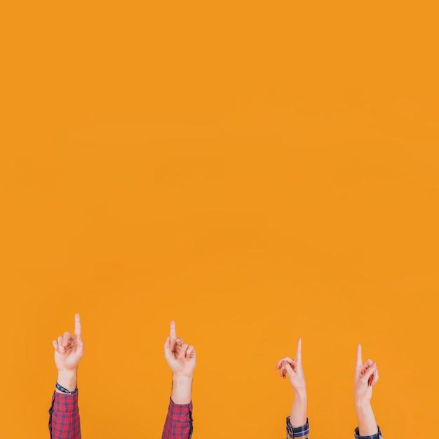 Nahaufnahme des mannes und der frau, die aufwärts seinen finger gegen einen orange hintergrund zeigen Kostenlose Fotos