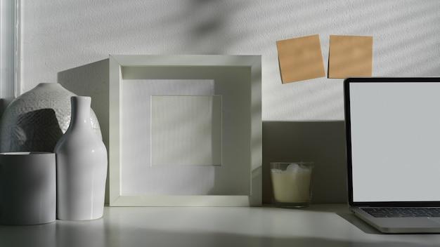 Nahaufnahme des minimalen arbeitsbereichs mit modellrahmen und modelllaptop mit anderen büromaterialien Premium Fotos