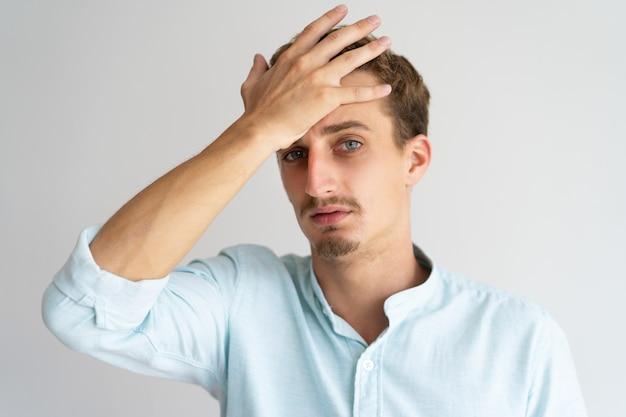 Nahaufnahme des müden enttäuschten blonden kerls mit gesichtspalmengeste. Kostenlose Fotos