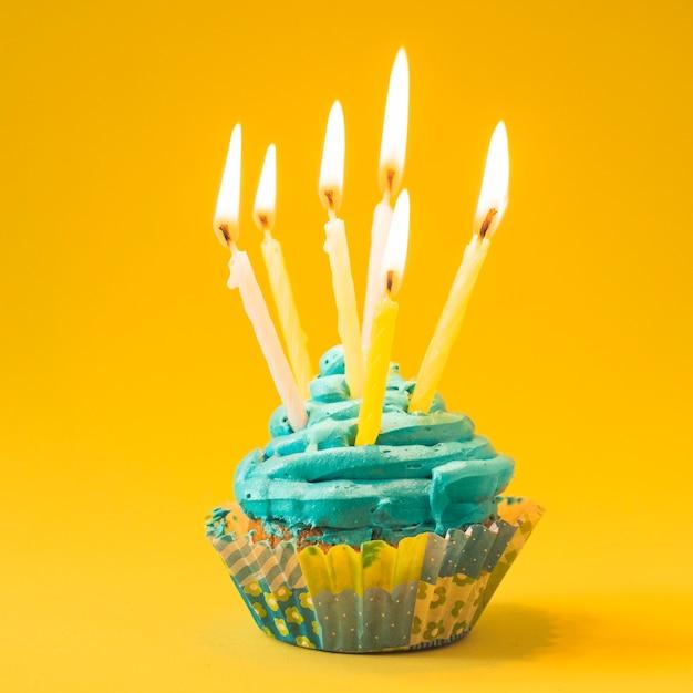 Nahaufnahme des muffins mit brennenden kerzen auf gelbem hintergrund Kostenlose Fotos