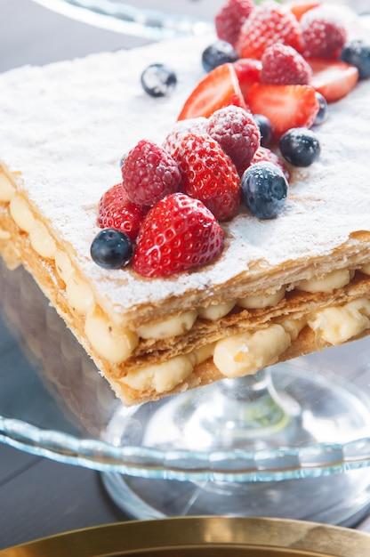 Nahaufnahme des napoleon-kuchens mit vanillepuddingcreme und reifen beeren Kostenlose Fotos