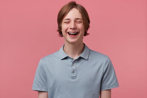 Nahaufnahme des netten blauäugigen ordentlich gekämmten jungen kerls mit zahnspangen auf den zähnen freudig lachend geschlossen seine augen des spaßes trägt polo-t-shirt sieht glücklich isoliert über rosa hintergrund aus Kostenlose Fotos