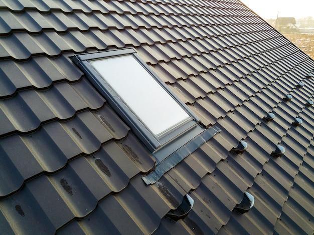 Nahaufnahme des neuen dachbodenplastikfensters, das im schindeldach des hauses installiert wird. professionell durchgeführte bau-, dach- und installationskonzepte. Premium Fotos