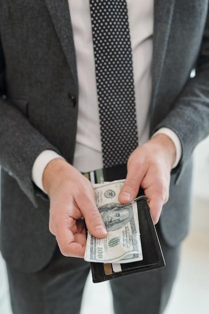 Nahaufnahme des nicht erkennbaren geschäftsmannes im grauen anzug, der geldbörse hält und bargeld für die zahlung vorbereitet Premium Fotos