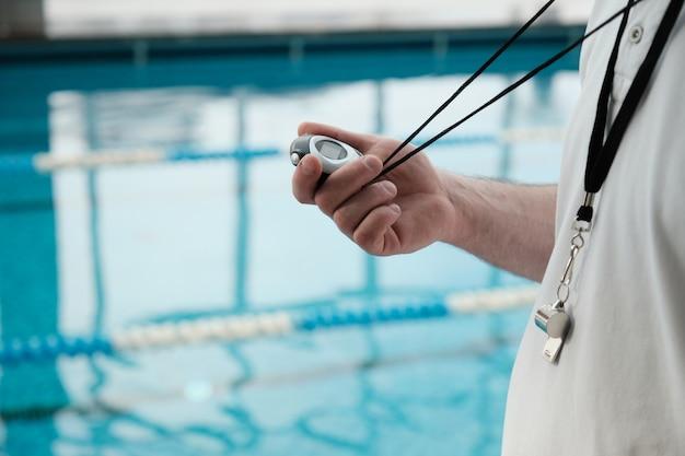 Nahaufnahme des nicht erkennbaren trainers mit pfeife unter verwendung der stoppuhr, während die leistung des athleten im schwimmbad bestimmt wird Premium Fotos
