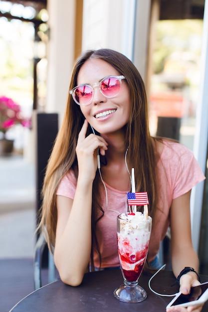 Nahaufnahme des niedlichen mädchens, das in einem café sitzt, das eis mit kirsche oben isst. sie trägt ein rosa oberteil und eine rosa brille. sie hört musik auf dem smartphone und lächelt. sie hat lange dunkle haare Kostenlose Fotos