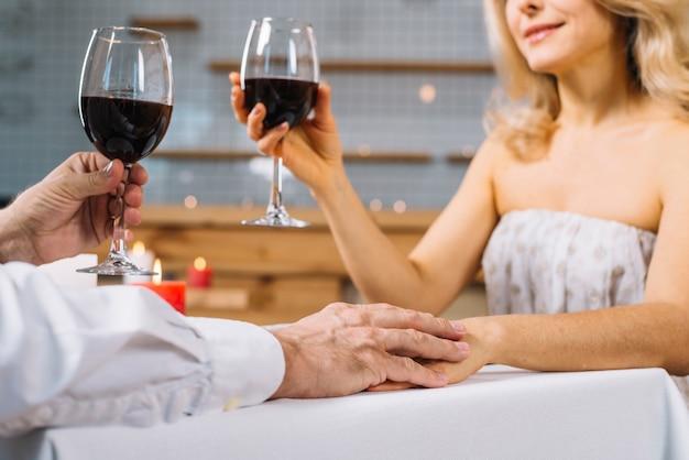 Nahaufnahme des paarhändchenhaltens am romantischen abendessen Kostenlose Fotos