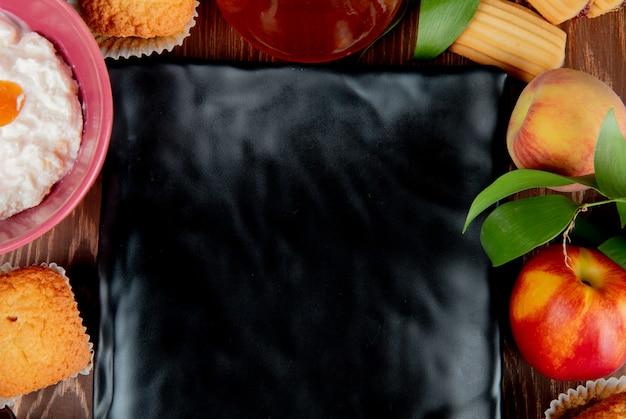 Nahaufnahme des pfirsich-pfirsich-marmeladen-cupcake-hüttenkäses mit platte in der mitte auf holztisch Kostenlose Fotos