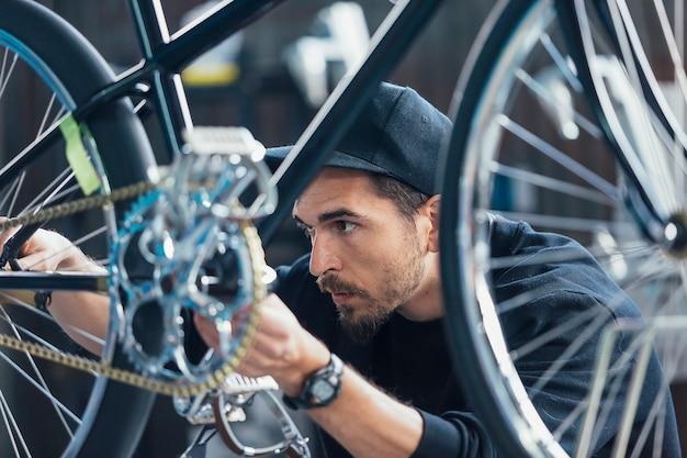 Nahaufnahme des professionellen konstrukteurs von fahrrädern, die kette betrachten Premium Fotos
