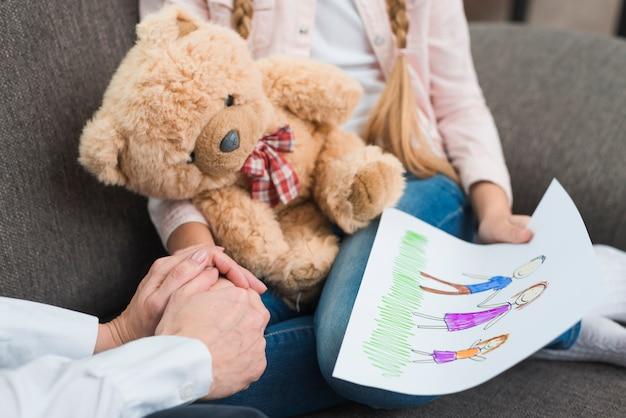 Nahaufnahme des psychologen hand eines mädchens halten zeichnungspapier mit gezogener familie halten Kostenlose Fotos