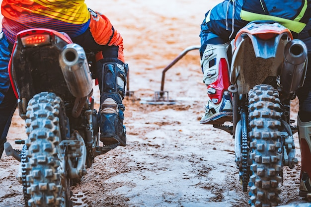 Nahaufnahme des radfahrers sitzend auf motorrad im ausgangspunkt vor dem anfang des rennens Premium Fotos