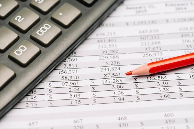 Nahaufnahme des roten farbigen bleistifts mit taschenrechner über dem finanzbericht Kostenlose Fotos