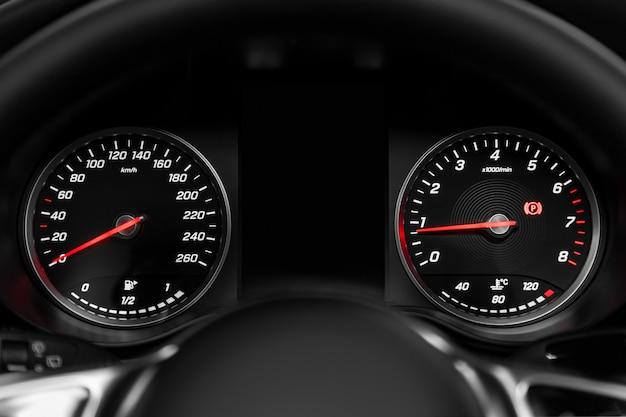 Nahaufnahme des runden armaturenbretts, des geschwindigkeitsmessers und des drehzahlmessers mit weißer hintergrundbeleuchtung. modernes auto interieur Premium Fotos