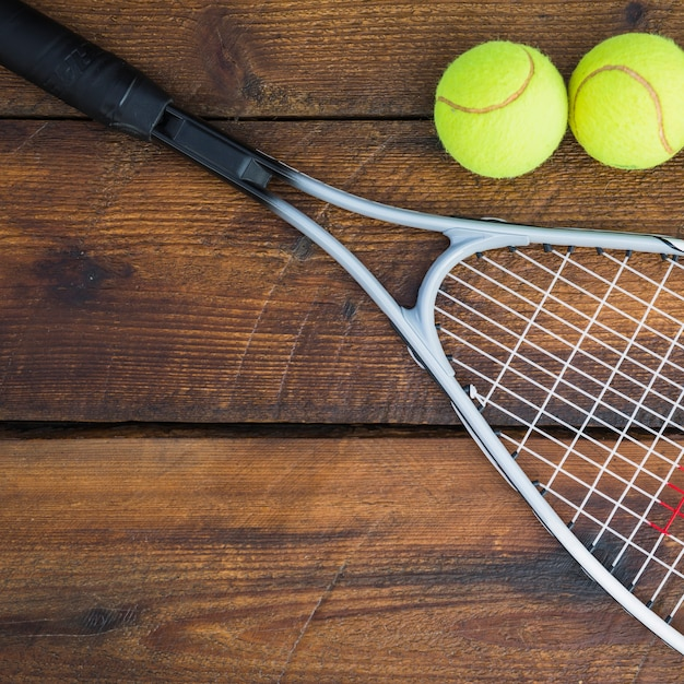 Nahaufnahme des schlägers mit zwei tennisbällen auf holztisch Kostenlose Fotos