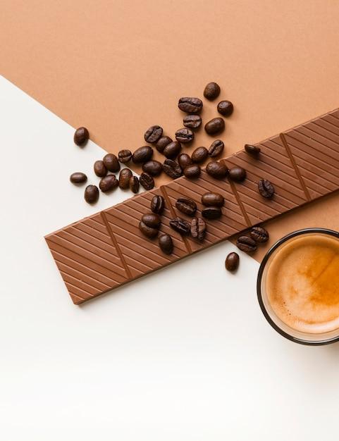 Nahaufnahme des schokoriegels und der röstkaffeebohnen mit kaffeeglas auf doppelhintergrund Kostenlose Fotos