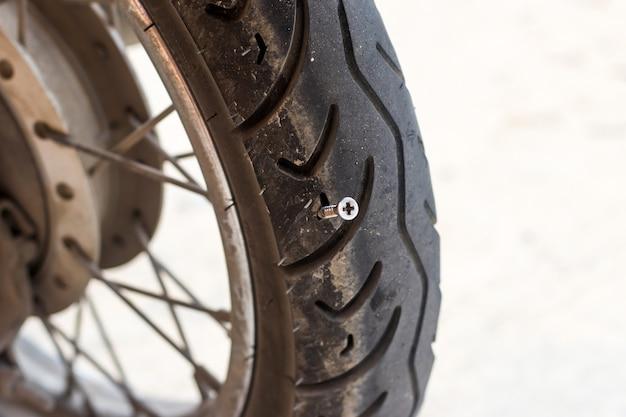 Nahaufnahme des schraubennagels, der motorradreifen oder fahrradreifen durchstößt Premium Fotos
