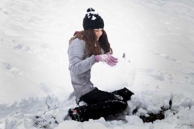 Nahaufnahme des spielerischen mädchens schneeball in der winterlandschaft machend Kostenlose Fotos